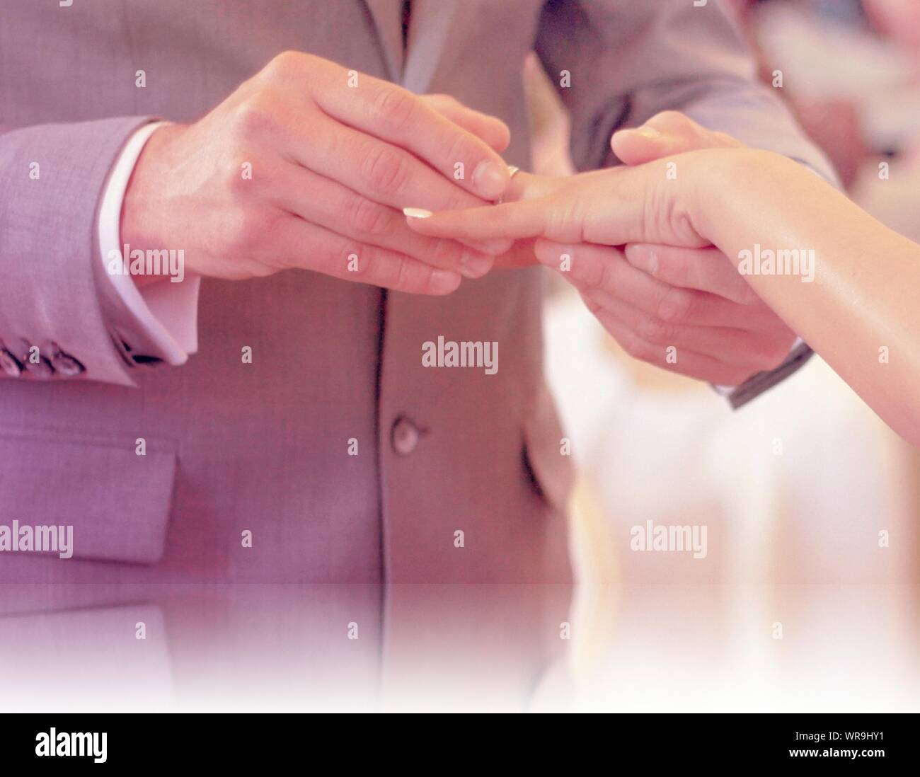 Man Sliding Ring On Woman Finger During Marriage Ceremony Stock Photo