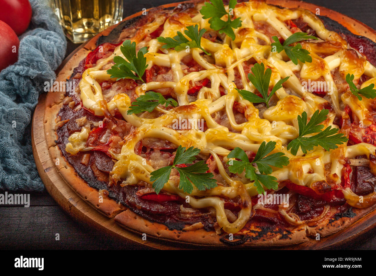 Homemade pizza with meat, sausage, cheese and tomatoes Stock Photo