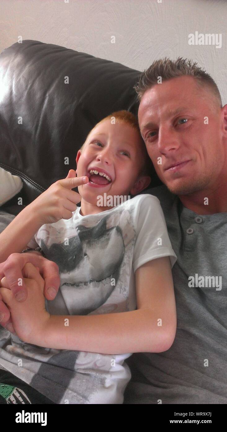 High Angle View Of Smiling Boy With Father Sitting On Sofa At Home Stock Photo