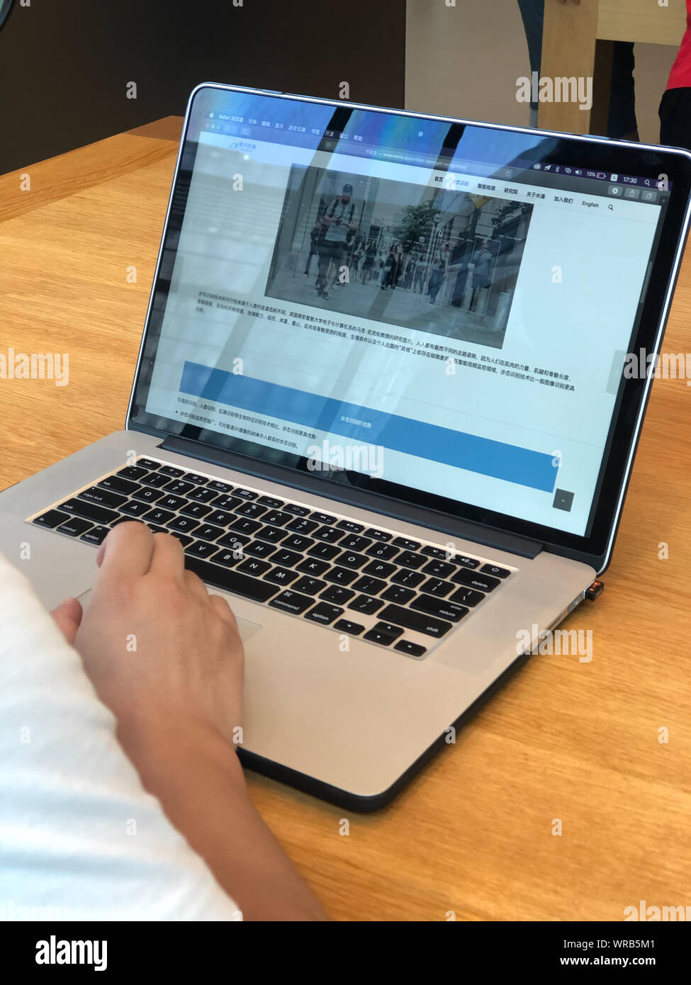 A Chinese netizen browses the introduction of Gait Recognition on the website of AI technology company Watrix on his Apple laptop computer in Beijing, Stock Photo