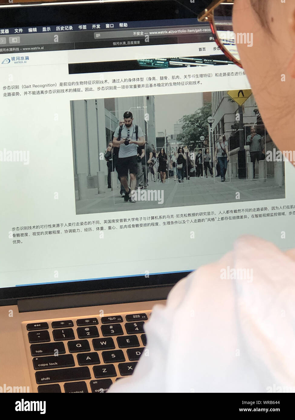 A Chinese netizen browses the introduction of Gait Recognition on the website of AI technology company Watrix on her Apple laptop computer in Beijing, Stock Photo