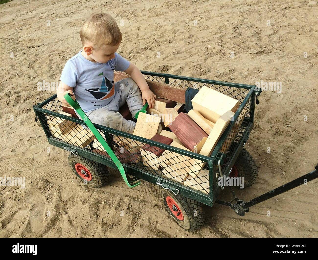High Angle View Of Boy With Toys Sitting In Vehicle Trailer At Beach - Stock Photo