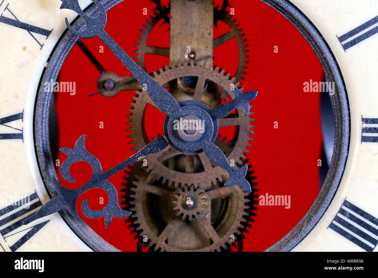 old metal dusty mechanical clock with moving gears and screws. Brass cog wheels, Close view of old rusty clock mechanism with gears and cogs. Stock Photo