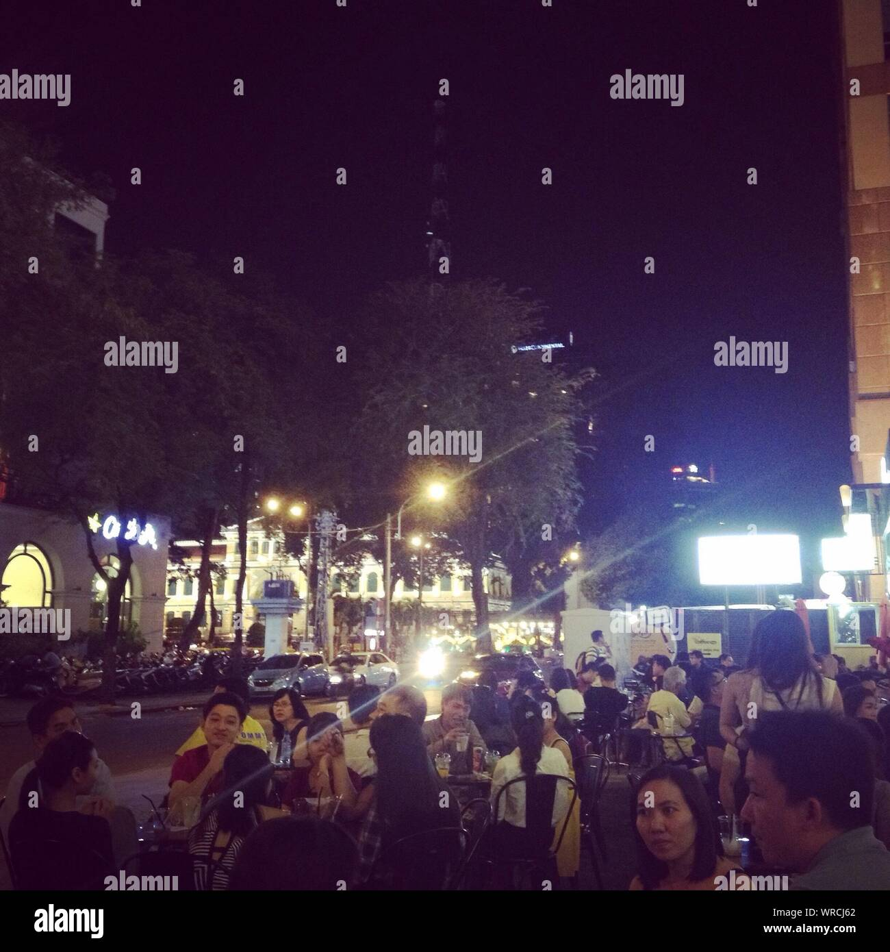 People Sitting At Sidewalk Cafe At Night Stock Photo