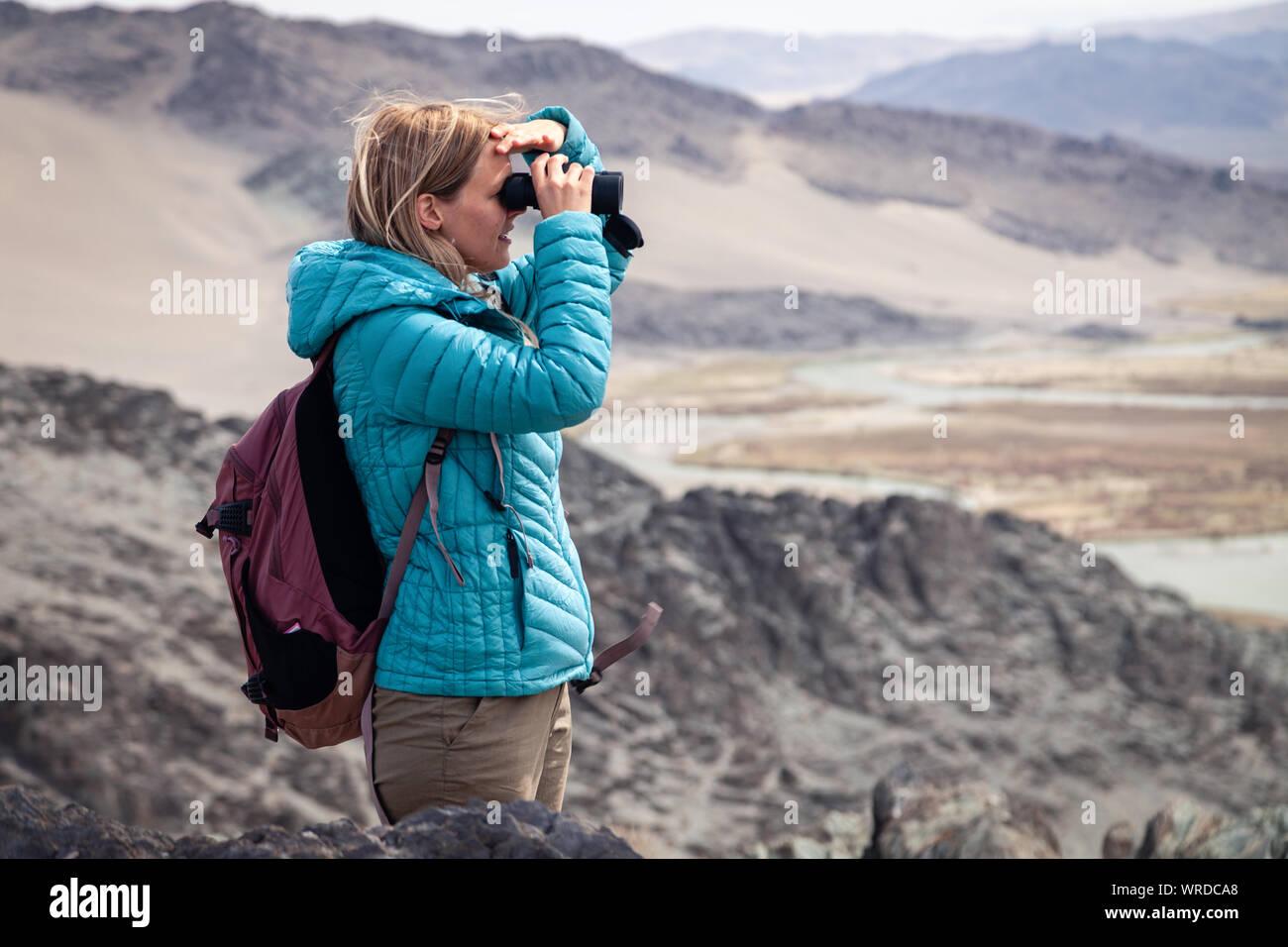 Mongolia Ulgii 2019-05-04 European beautiful girl in blue jacket looking through binocular into the distance, eagle watching, hiking, climbing, walkin Stock Photo