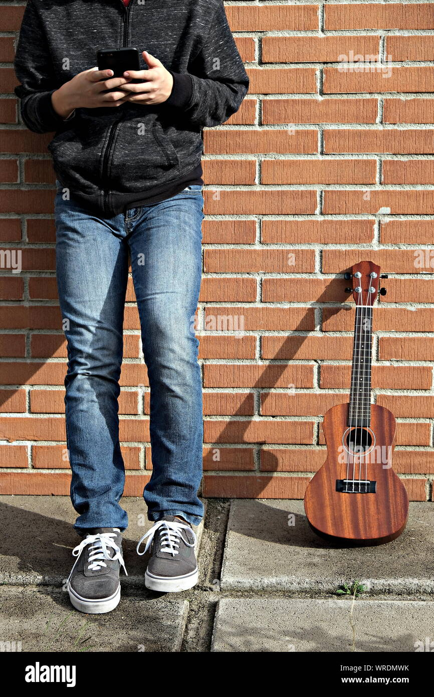 Young Ukulele Player On Break Checking The Smartphone Stock Photo Alamy