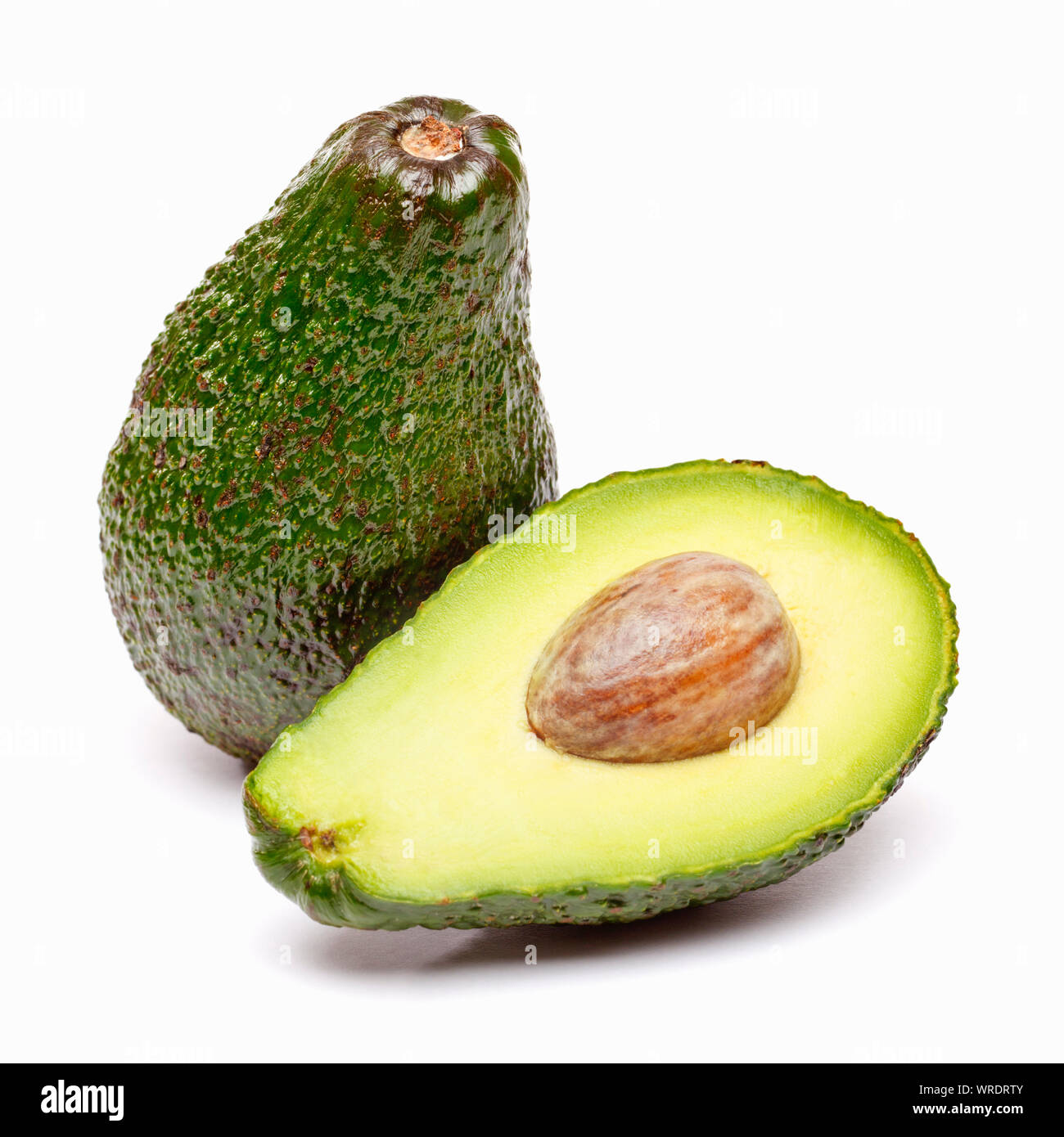 Avocados, whole and sliced in half on a white background Stock Photo