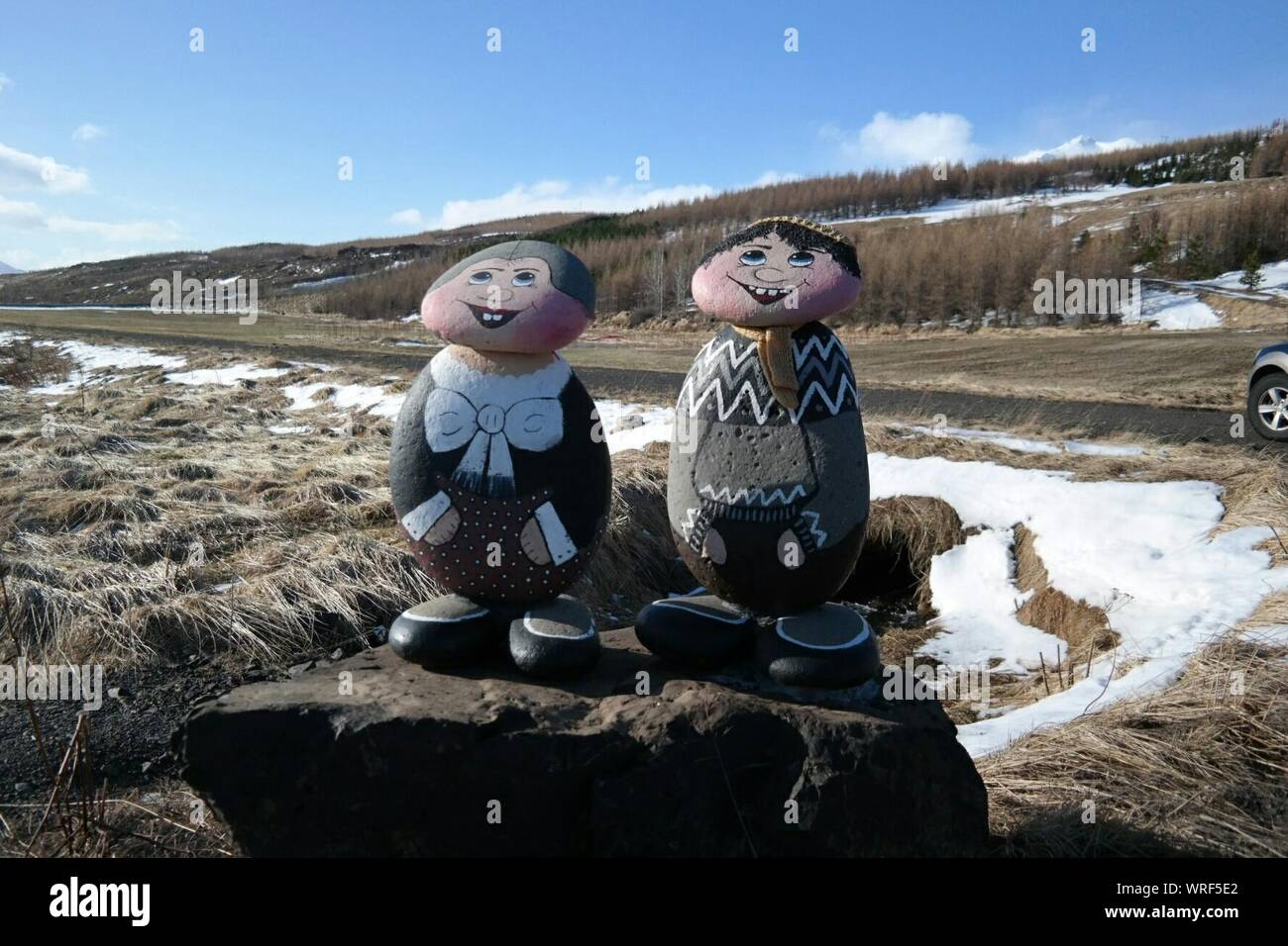 Humans Painted On Stones Against Landscape Stock Photo