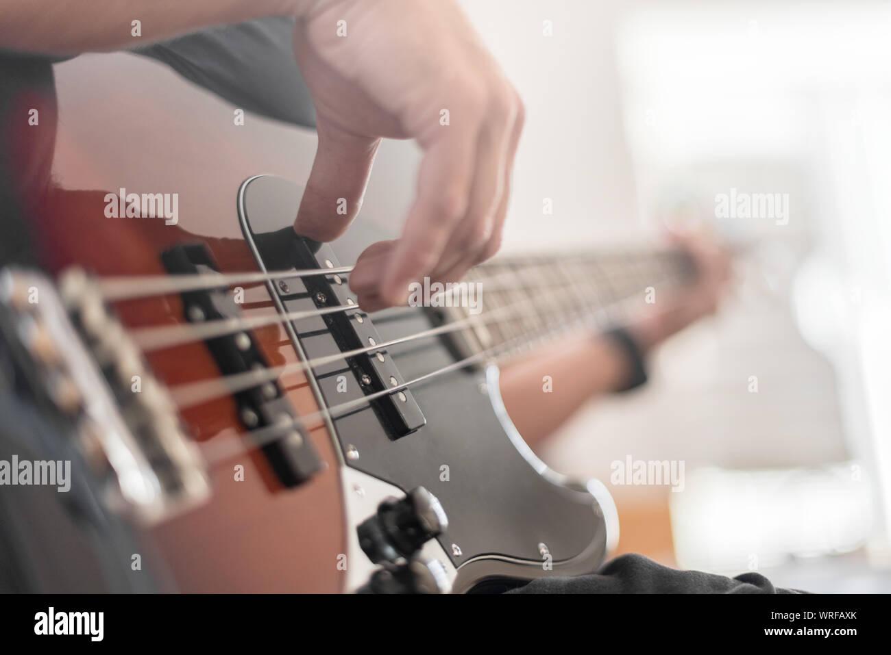 A man plays a bass guitar Stock Photo