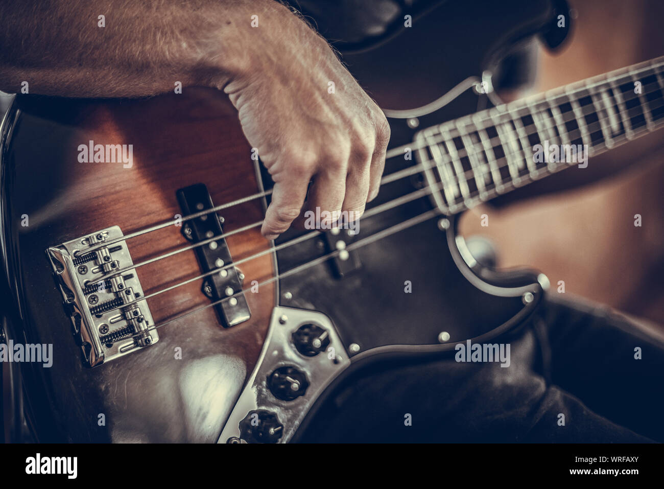 A man plays a bass guitar Stock Photo