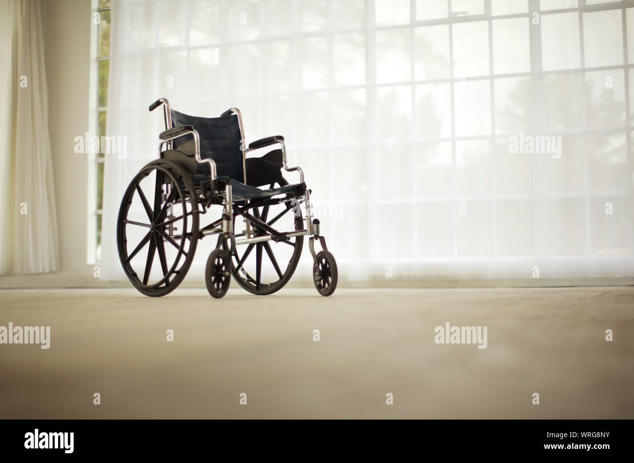 Wheelchair sitting in an empty room. Stock Photo