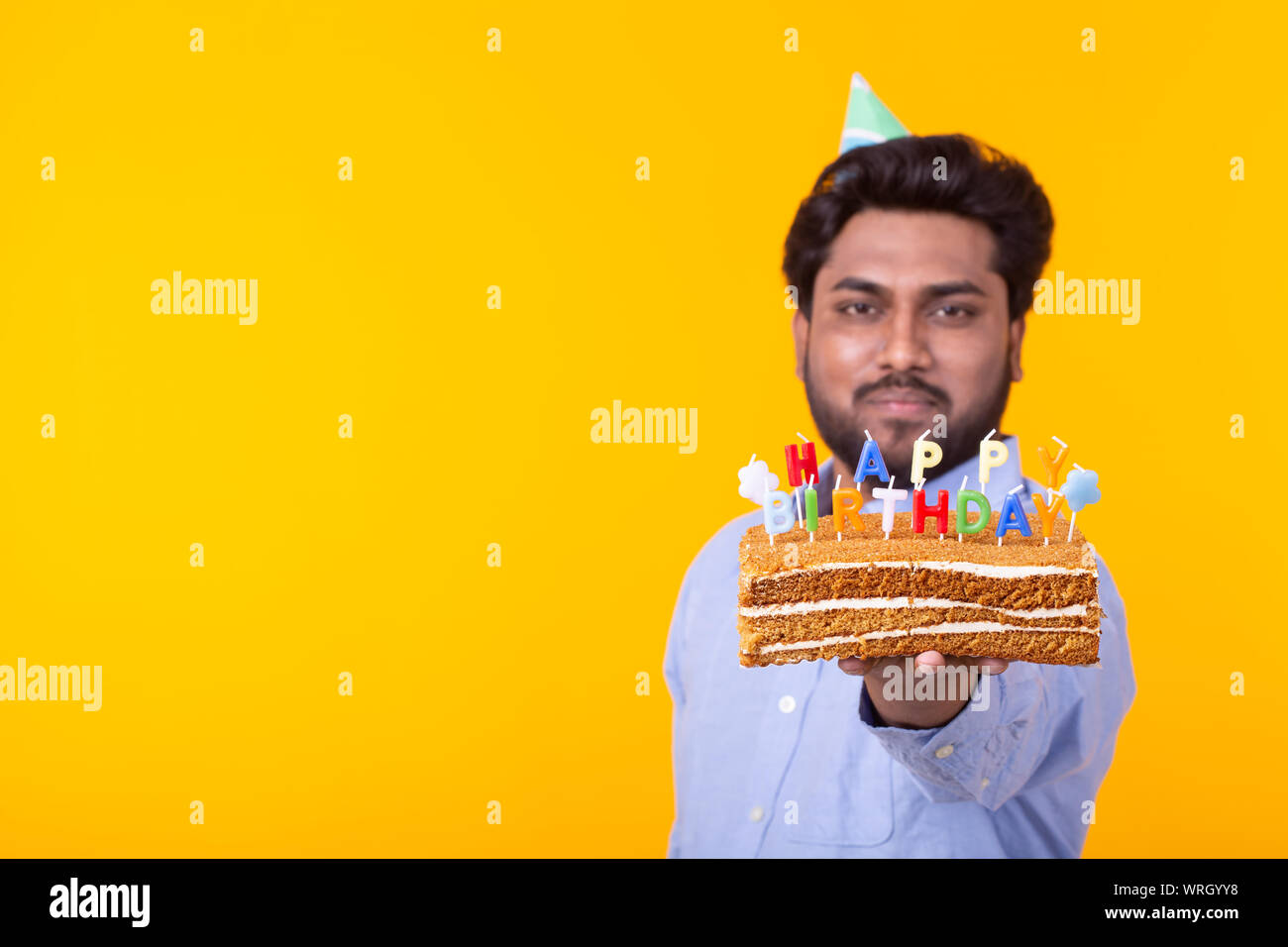 Crazy cheerful young indian man in paper congratulatory hat holding cakes  happy birthday standing on a yellow background. Jubilee congratulations  conc Stock Photo - Alamy