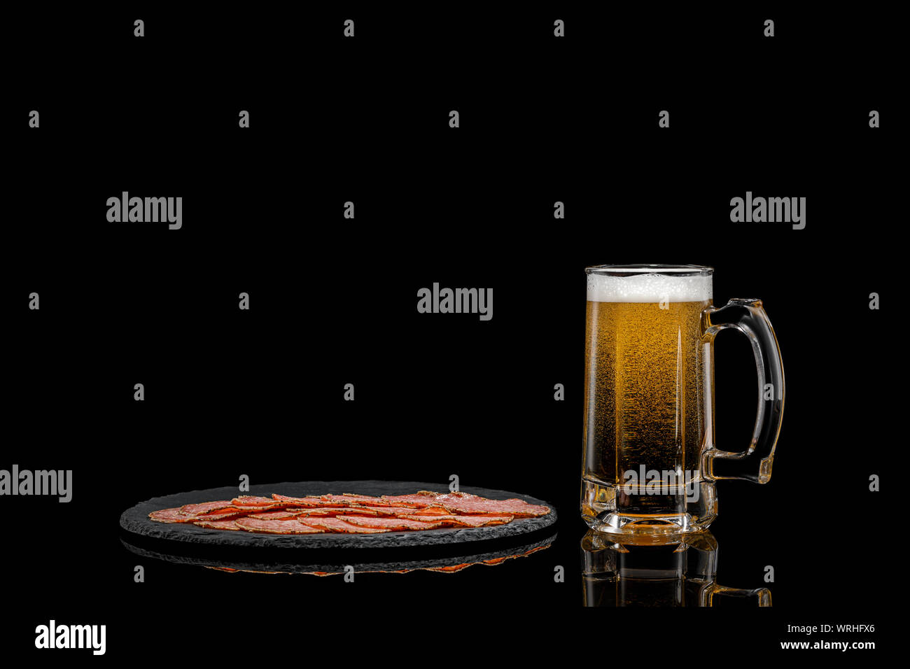 glass of beer and delicious sliced sausages on stone boardon black background. copy space Stock Photo