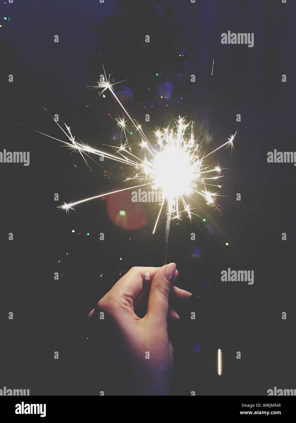 Close-up Of Hand Holding Diwali Cracker Against Black Background Stock Photo