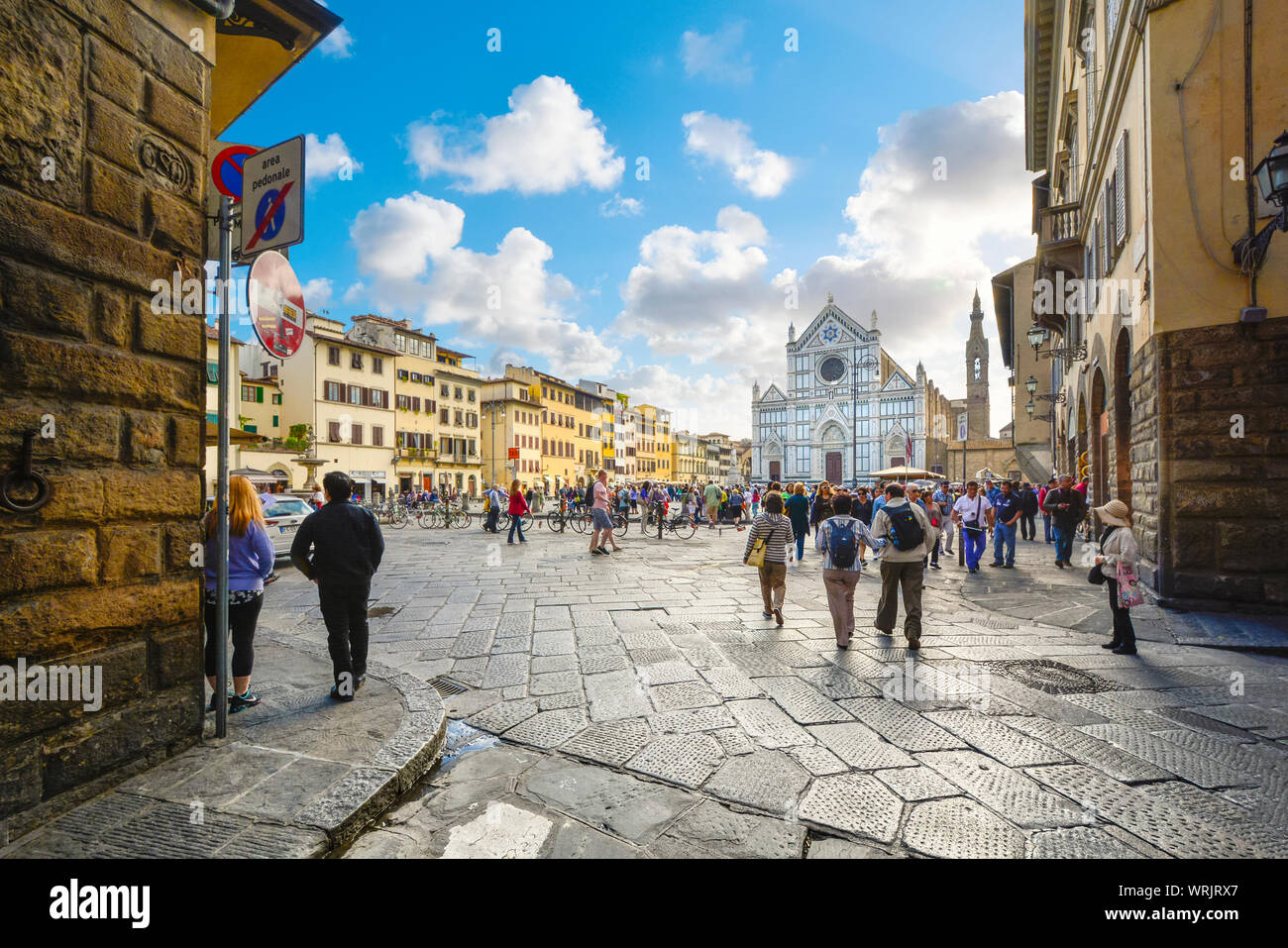 Late summer afternoon in the Tuscan city of Florence as tourists walk through Piazza Santa Croce towards the Basilica Stock Photo