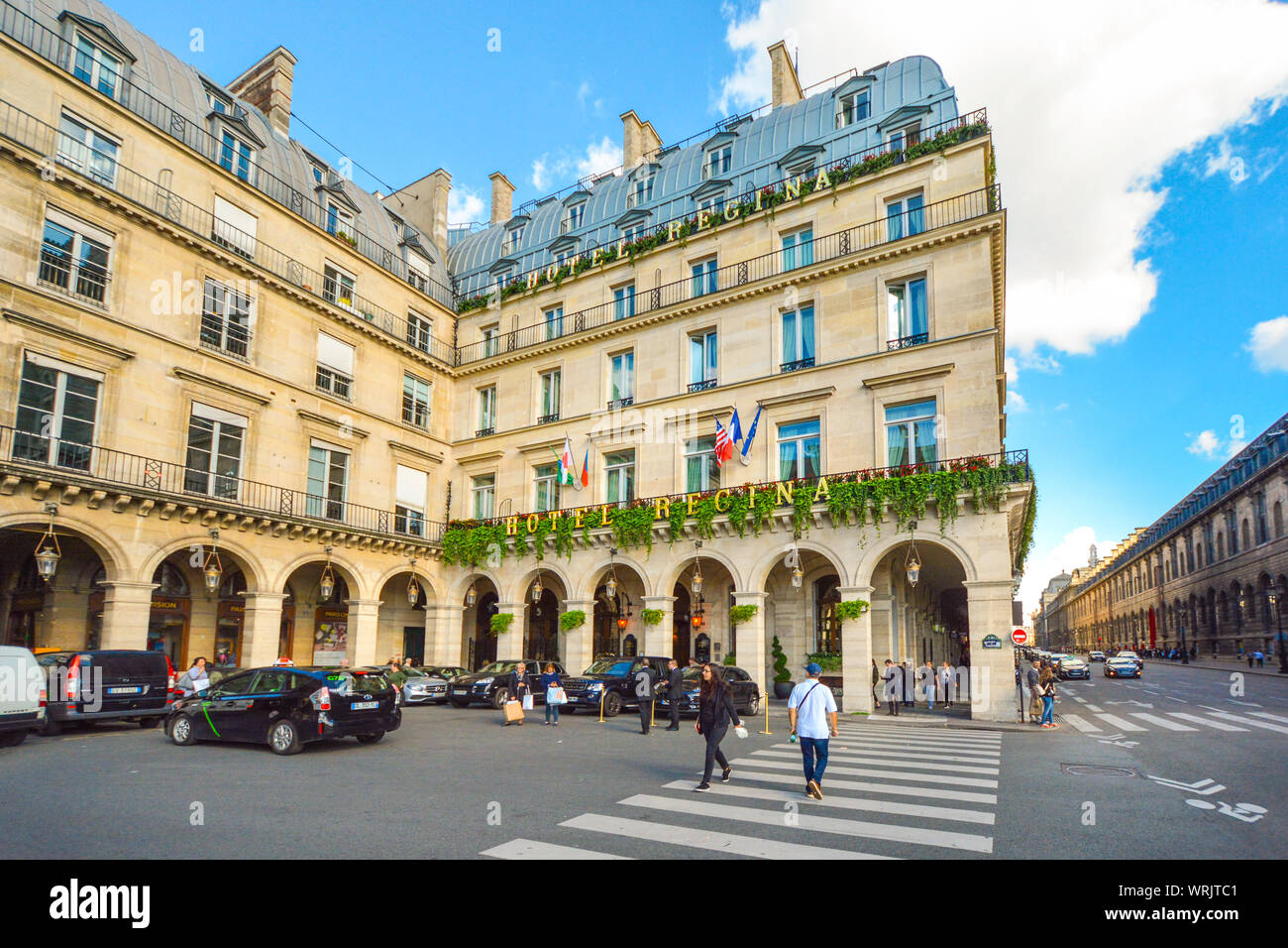 Cars park in the Place des Pyramides as tourists and pedestrians cross the intersection in front of a luxury hotel on Rue du Rivoli Stock Photo