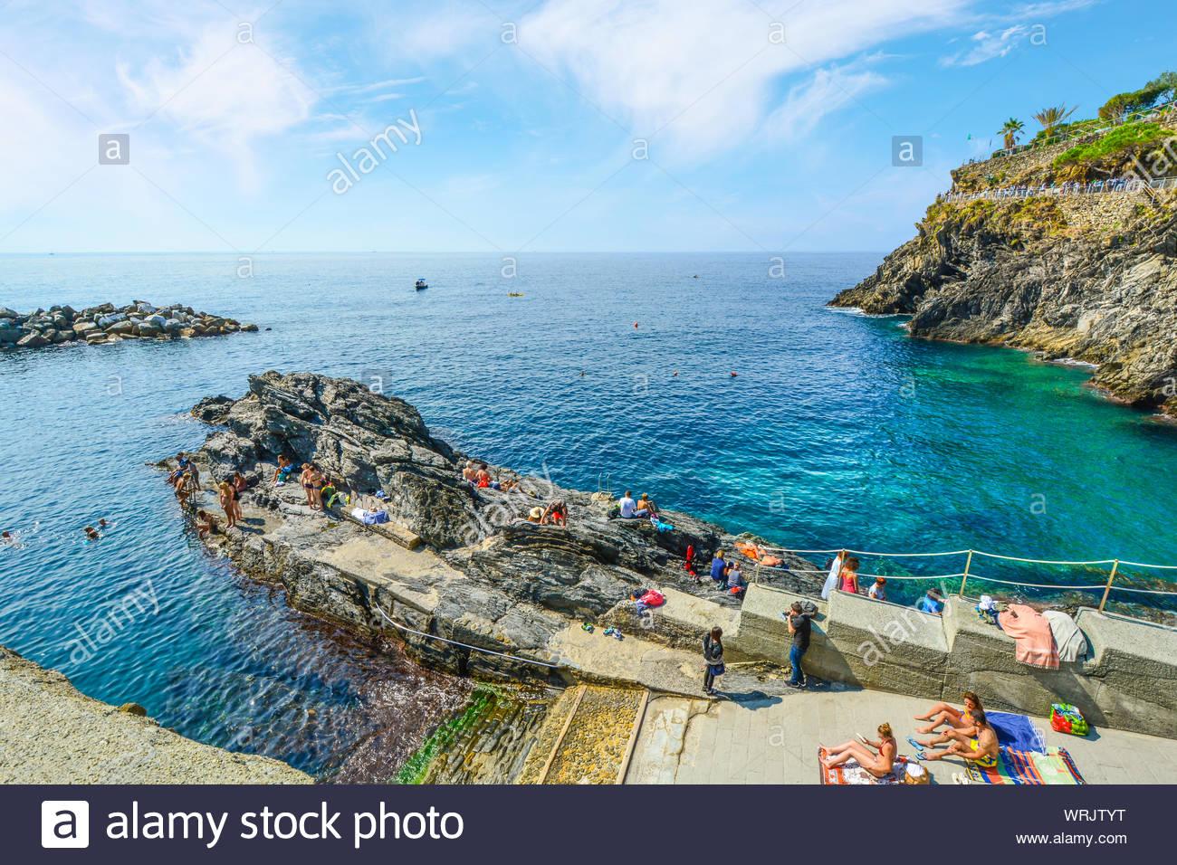 Tourists swim in the sea and sunbathe near the the rocky coastline of Manarola, Italy, part of the Cinque Terre. Stock Photo