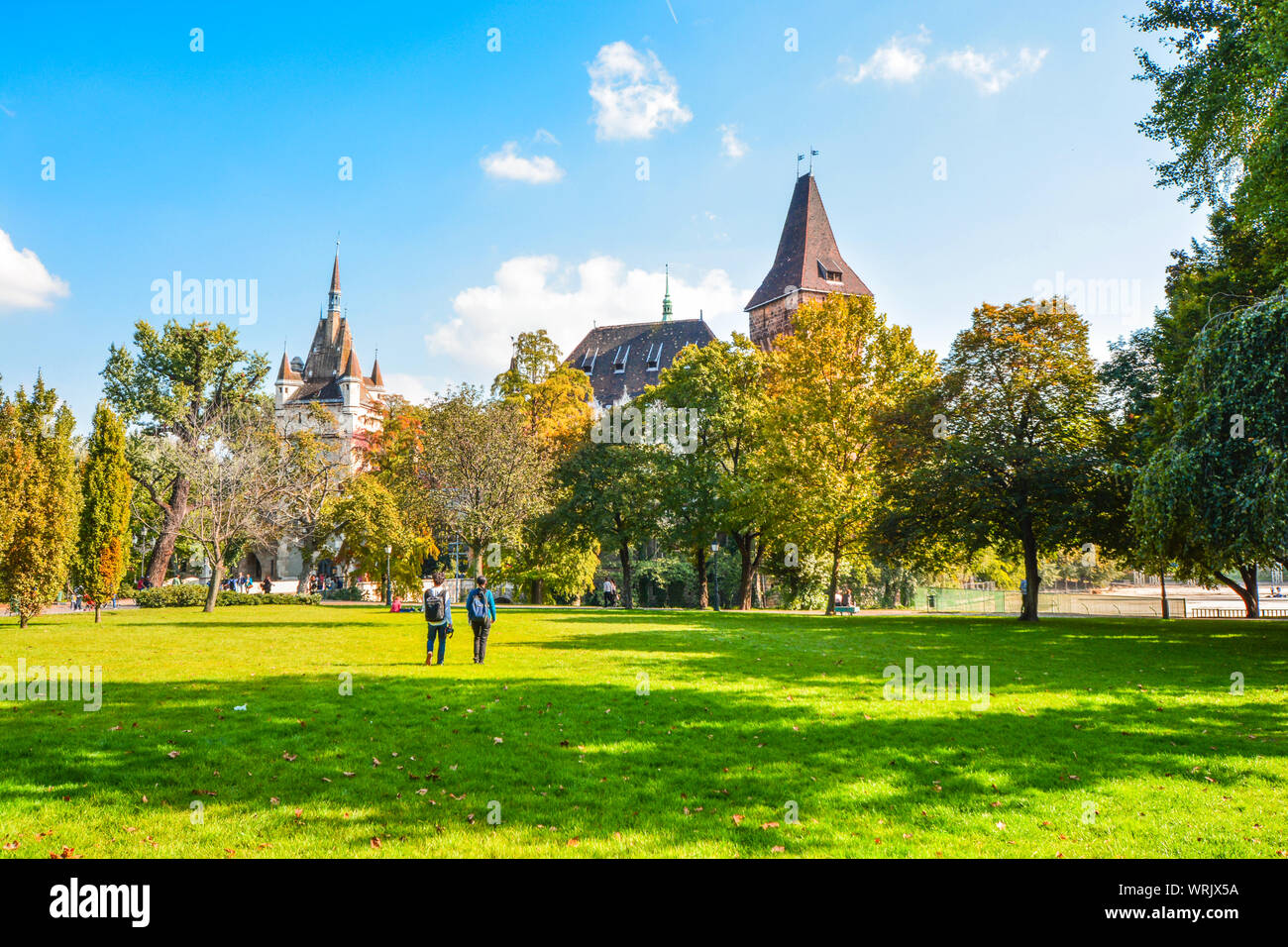 A young couple stops to admire the towers of Vajdahunyad Castle inside the City Park on a clear autumn day in Budapest, Hungary Stock Photo
