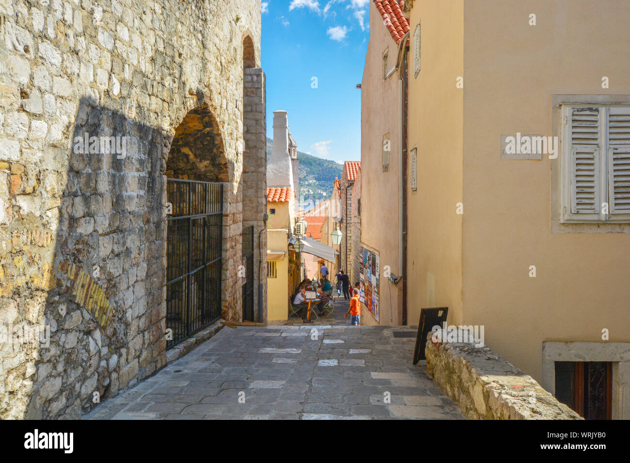 Tourists enjoy a meal at a sidewalk cafe on one of the narrow alleys inside the ancient walled city of Dubrovnik, Croatia. Stock Photo