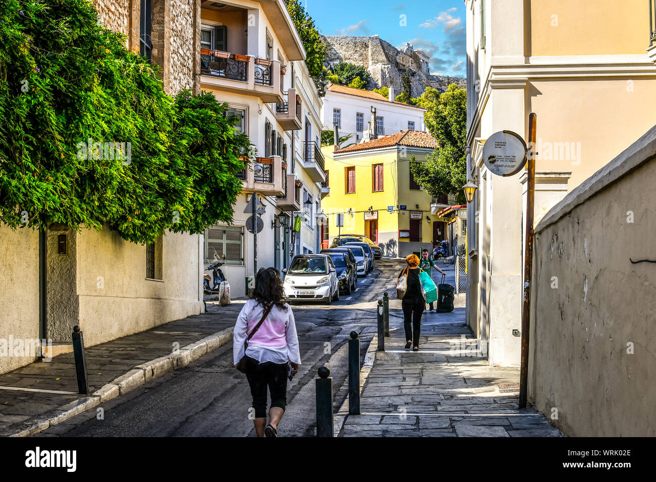 Local Greeks walk through a residential neighborhood near the Plaka District under the Parthenon and Acropolis Hill in Athens, Greece. Stock Photo