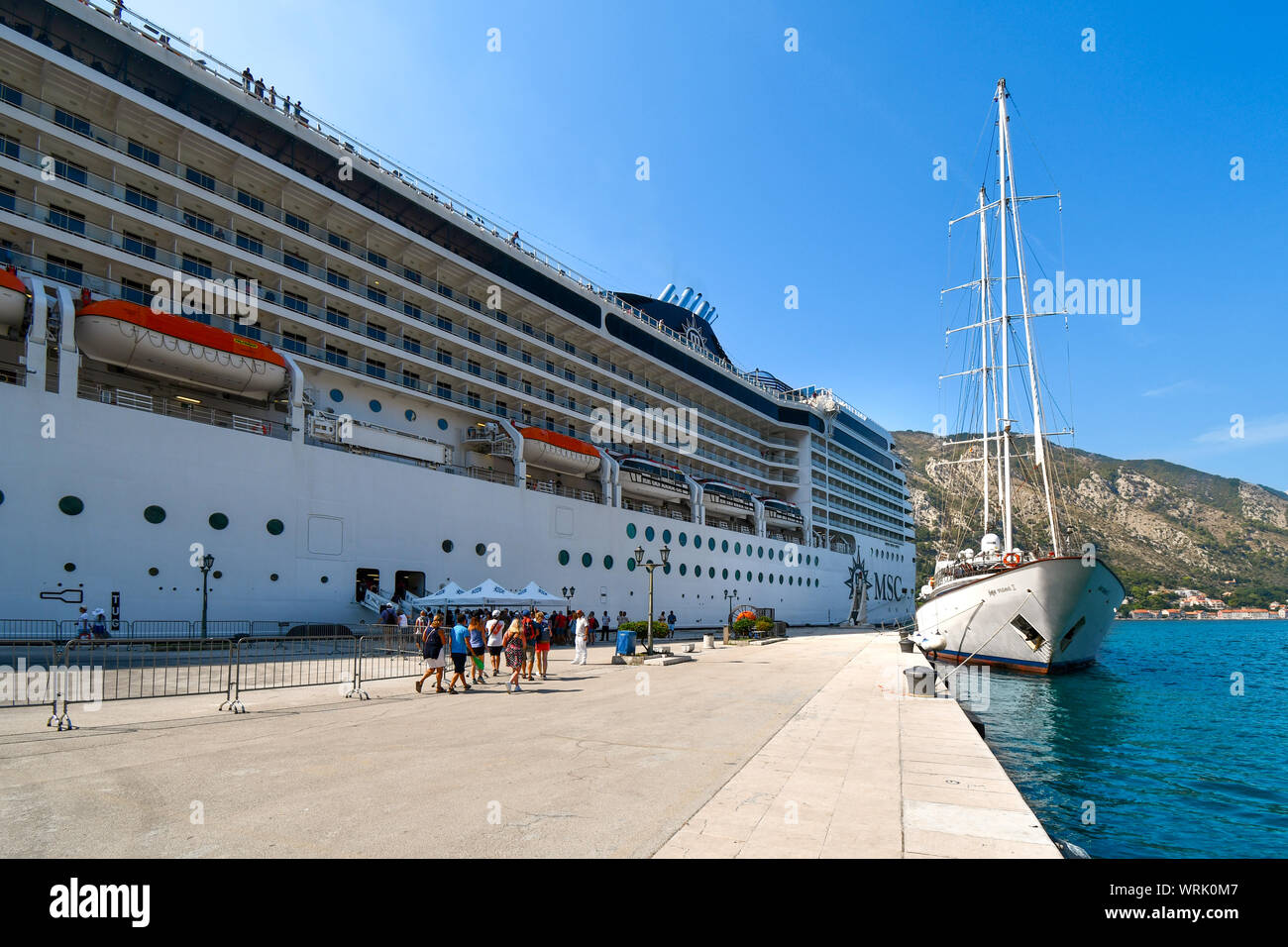 Tourists arrive back at a massive cruise ship in the cruise port of the ancient city of Kotor, Montenegro. Stock Photo