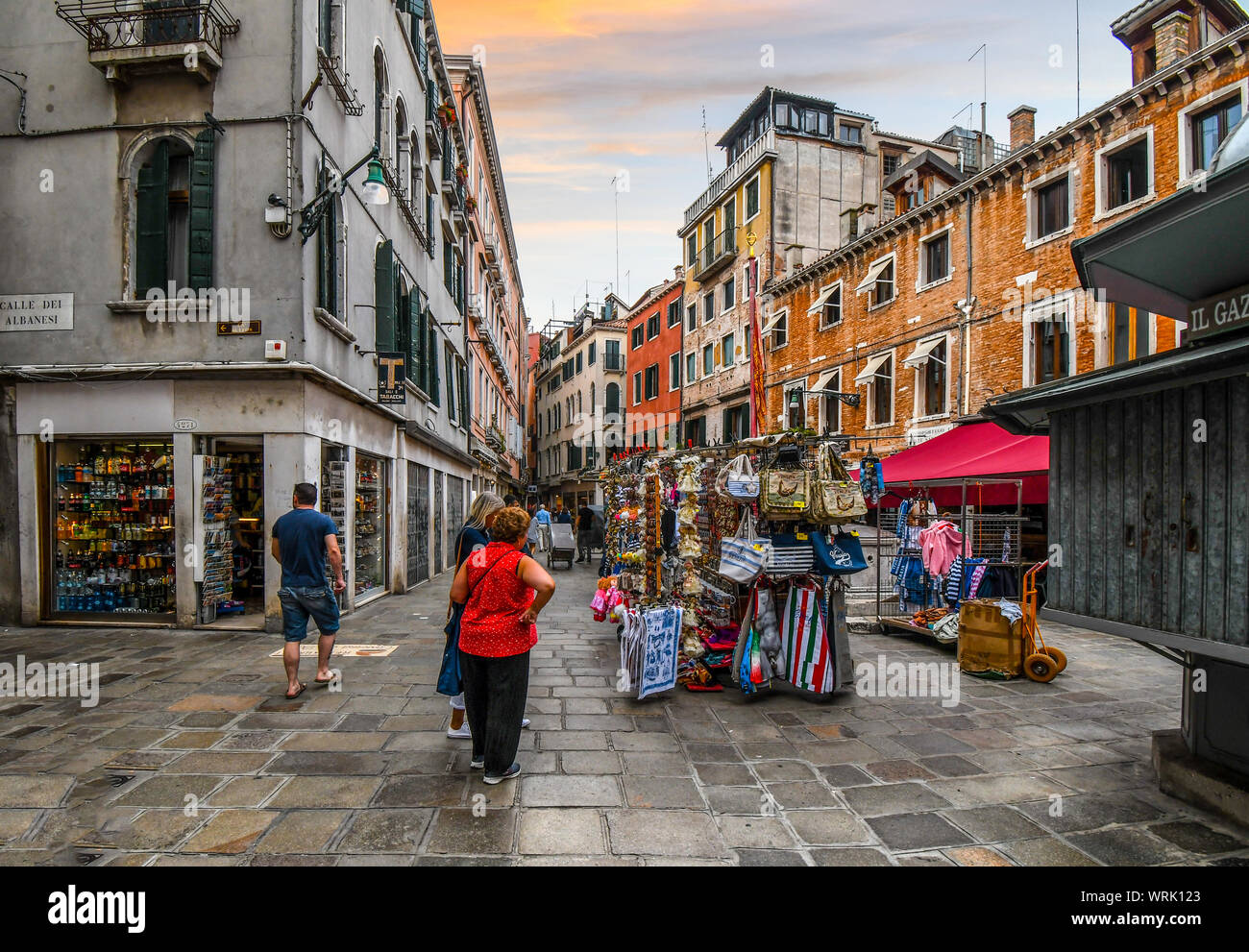 Tourists shop for souvenirs and purses in front of a market as they sightsee on an early morning in the historical center of Venice, Italy. Stock Photo
