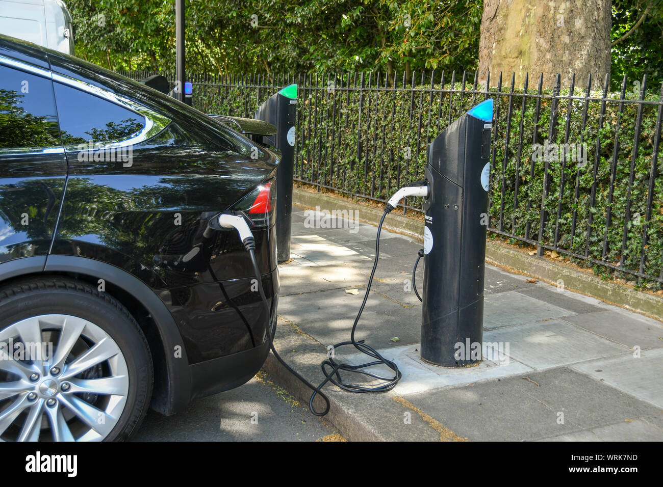 LONDON, ENGLAND - JULY 2018:  Care plugged into a charging point for electric cars kerb-side on a street in central London Stock Photo