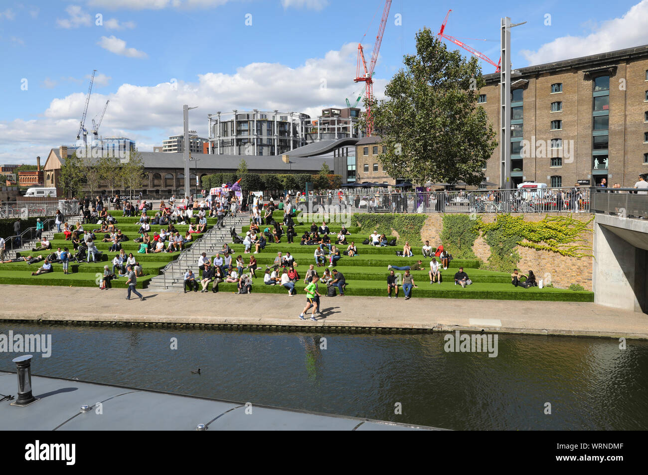 The grass steps leading down from Granary Square to Regents Canal at Kings Cross, NC1, in the autumn sunshine, in north London, UK Stock Photo