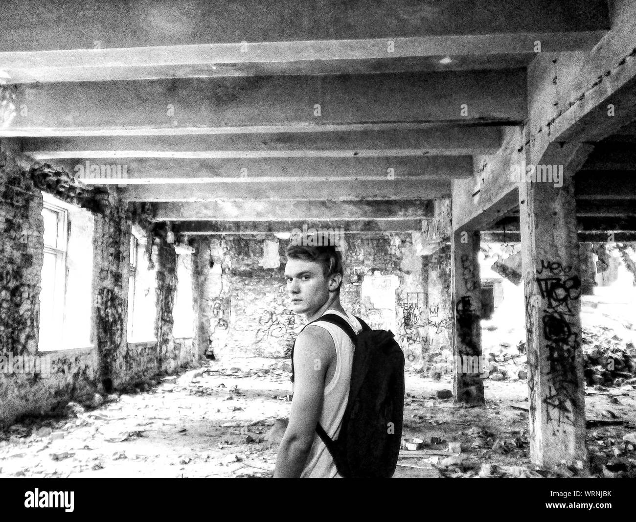 Portrait Of Man Carrying Backpack Standing At Abandoned Old Building Stock Photo Alamy