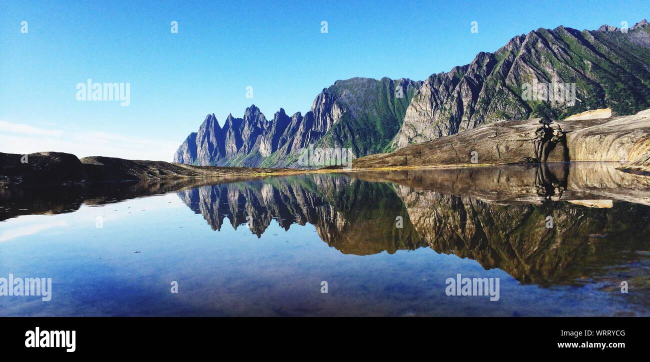 Reflection Of Mountain In Lake Against Clear Blue Sky Stock Photo