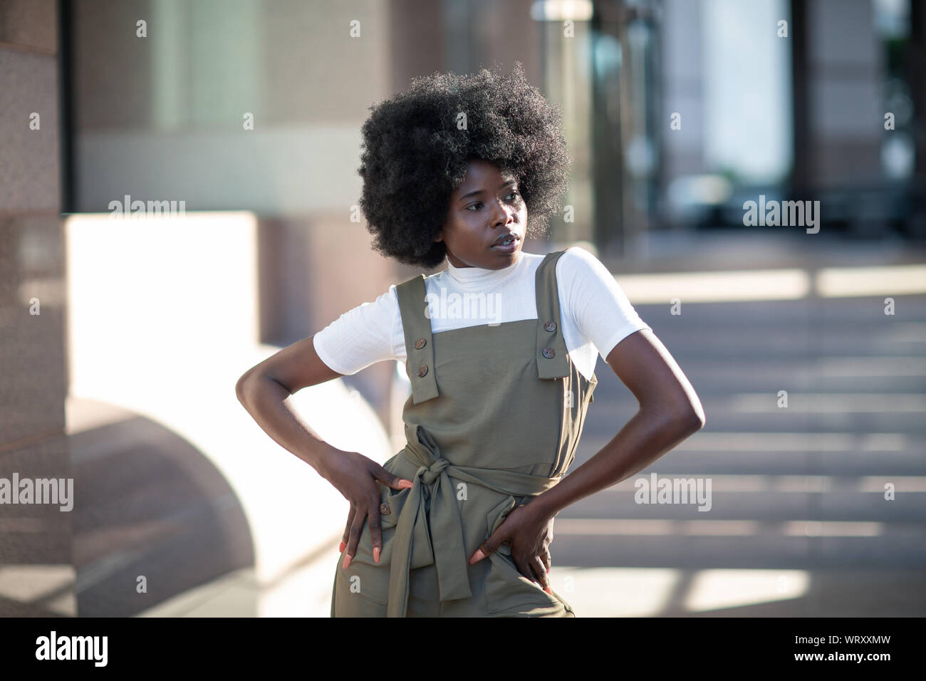 Beautiful African American girl with curly hair, fashionable overalls, and white turtleneck. Stock Photo