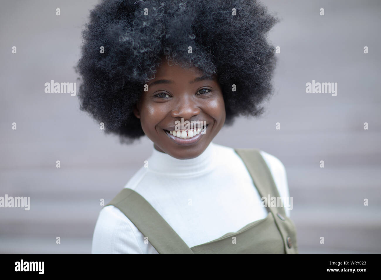 Gorgeous looking young black girl smiling broadly looking at the camera, artistick urban background, perfect for dentist company. Stock Photo