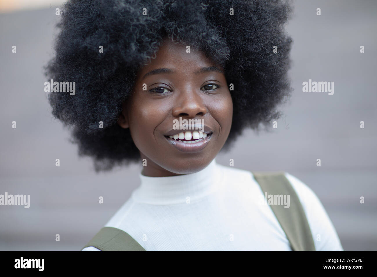 Gorgeous looking young black girl smiling broadly looking at the camera Stock Photo