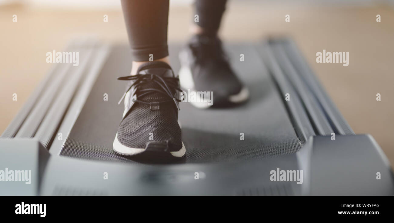 Close-up view of athletic woman running in jogging sneakers on treadmill inside the gym Stock Photo