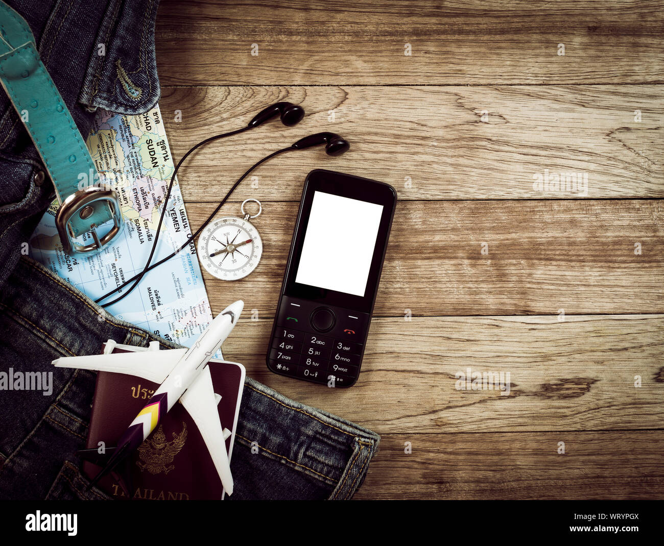 Travel concept, denim bag, pants, belt, map, earphones, compass and mobile phone on vintage wooden table Stock Photo