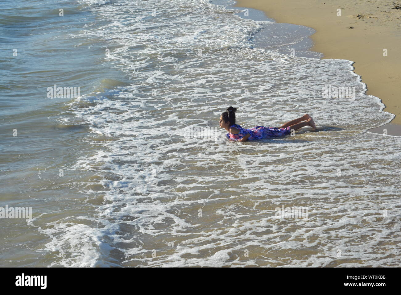 Girl on sandy beach playing in surf waves. Stock Photo