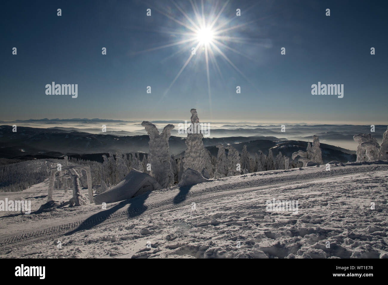 spectacular view with many mountain ranges, sun with clear sky and fog in valleys from Lysa hora hill in winter Moravskoslezske Beskydy mountains in C Stock Photo