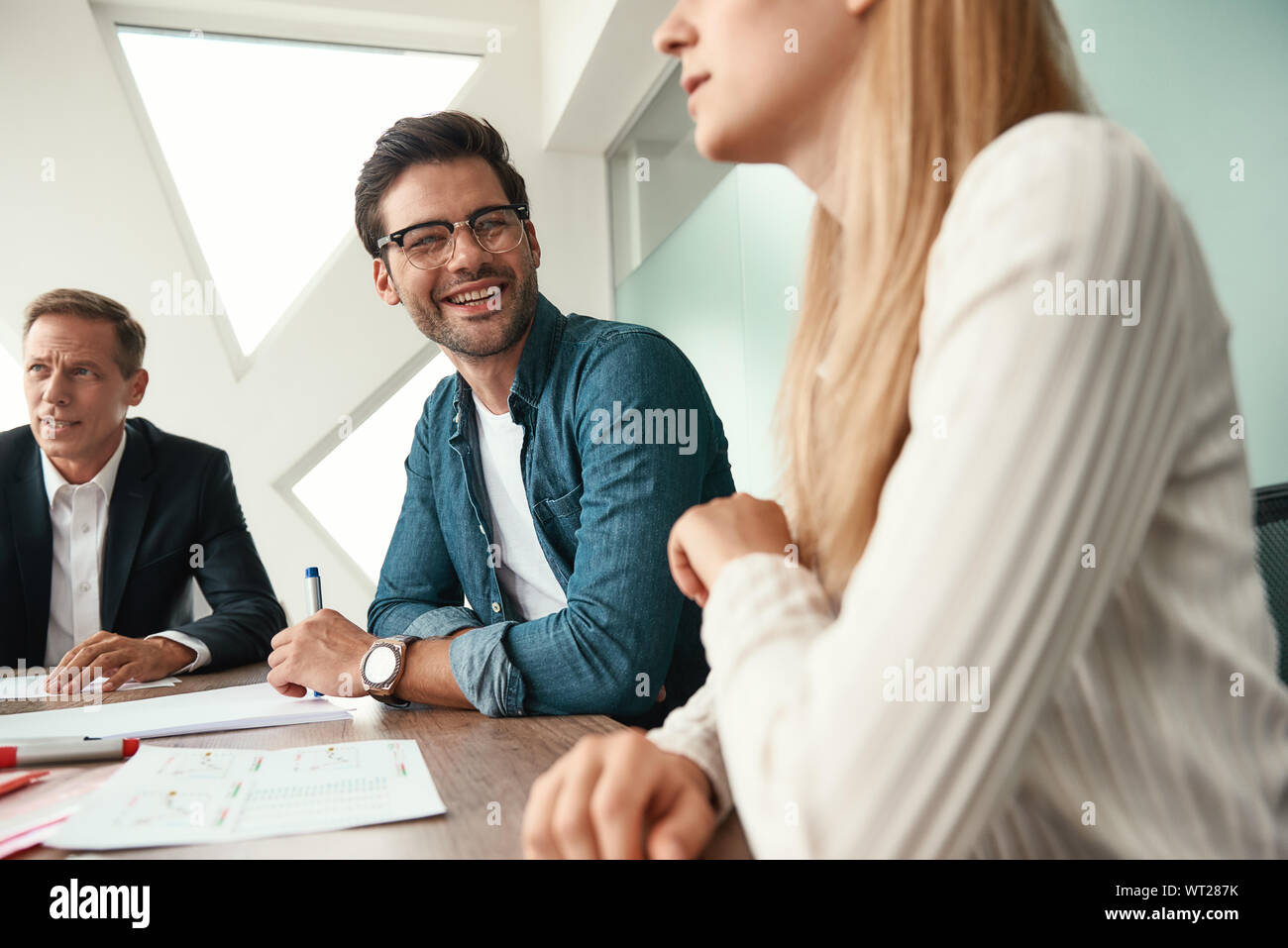 Morning meeting. Business team discussing something and smiling while sitting in the modern office. Brainstorming. Team work Stock Photo