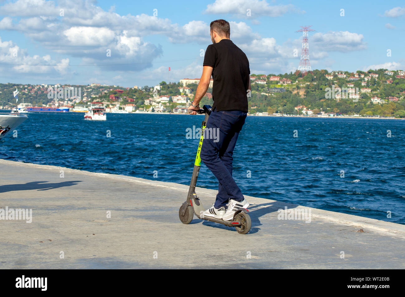 Young man riding Marti Tech, scooter rental service, rented electric scooter on the seaside. Bosphorus view with clouds in the background. Stock Photo