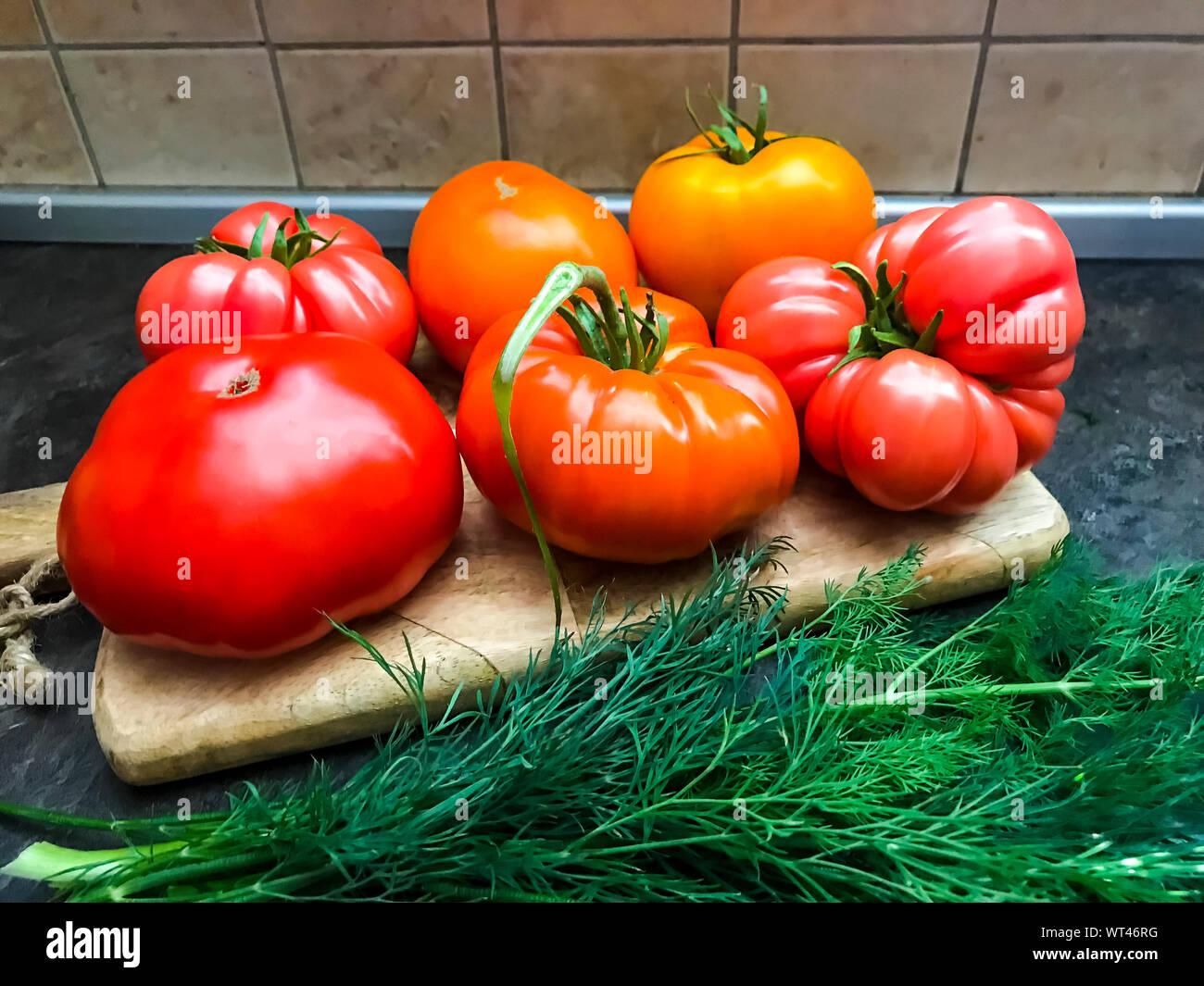 Multicolored fresh tomatoes on wooden kitchen board. Studio Photo Stock Photo
