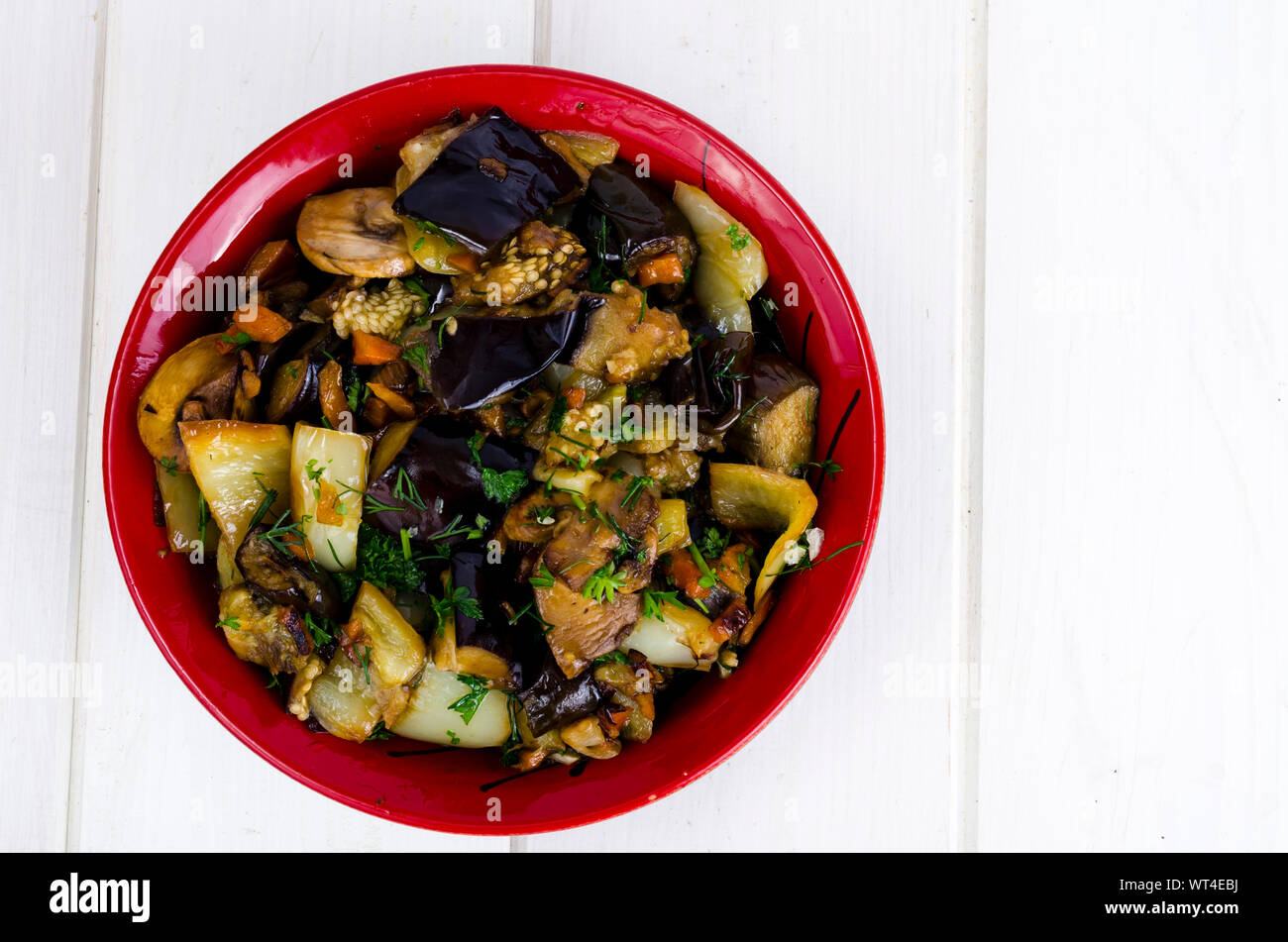Vegetable saute with eggplants in ceramic bowl on white wooden table. Studio Photo Stock Photo