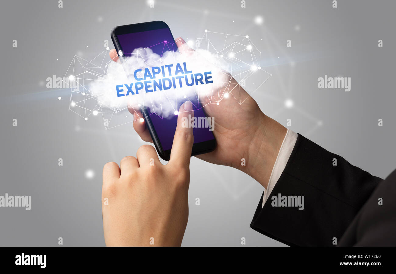 Female hand touching smartphone with CAPITAL EXPENDITURE inscription, cloud business concept Stock Photo