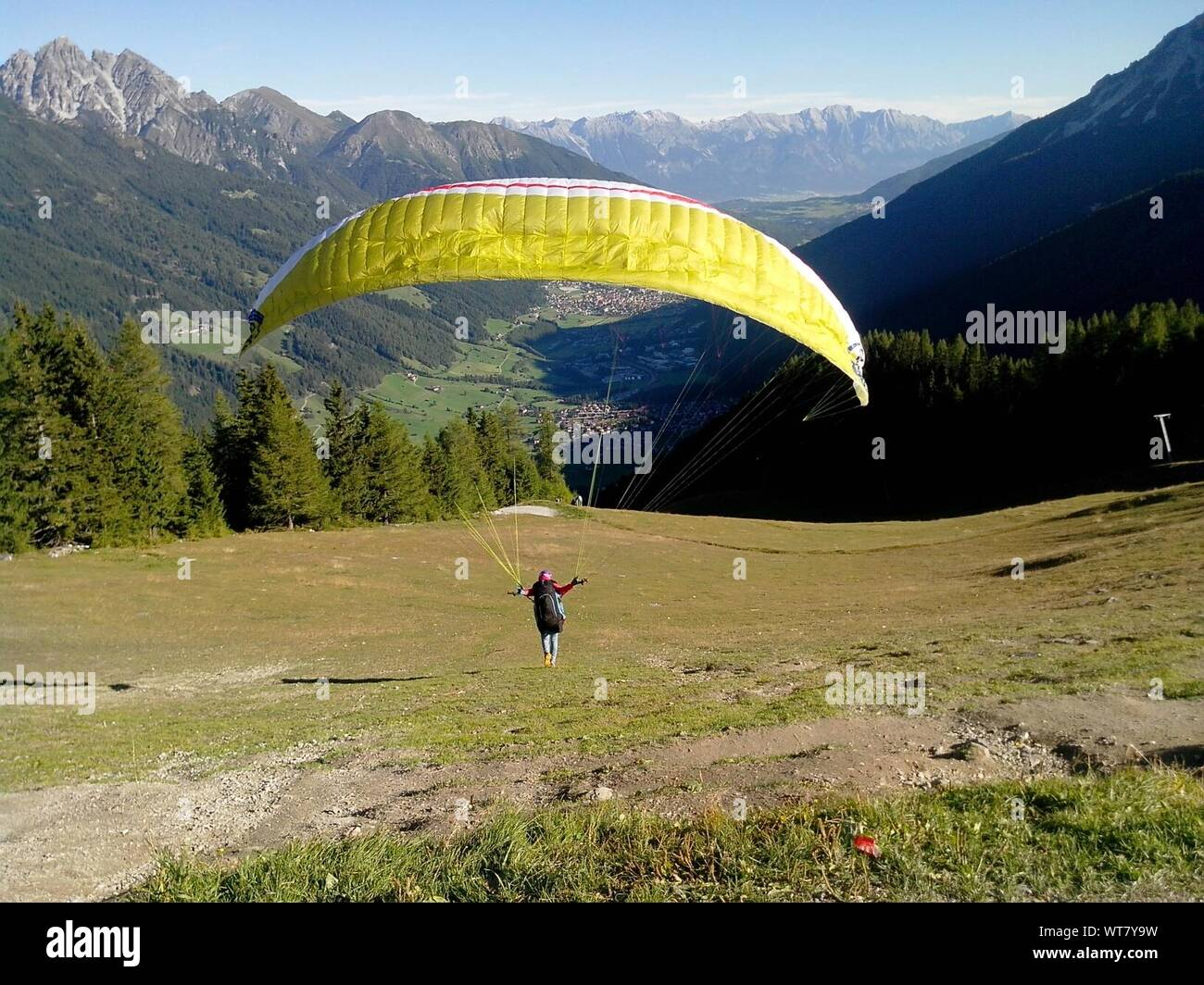 Paraglider Landing On A Grassy Field Against Mountains Stock Photo