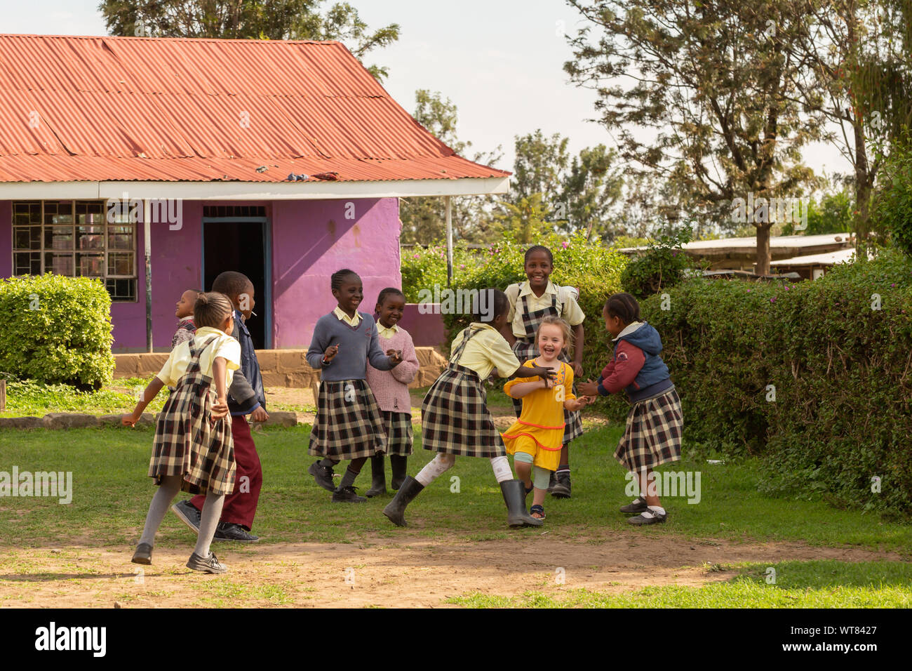 Imani Junior Academy, Nanyuki, Laikipia county, Kenya – June 13th, 2019: Candid photograph of young school children playing with a white girl who was Stock Photo