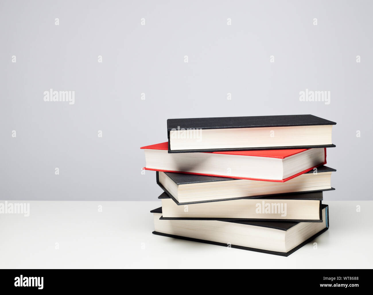 Stack of four black and one red hardback books on a table Stock Photo