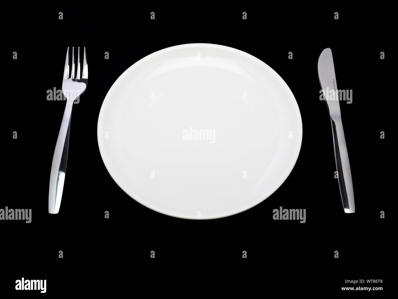 Place setting, white plate, knife and fork on a black background Stock Photo