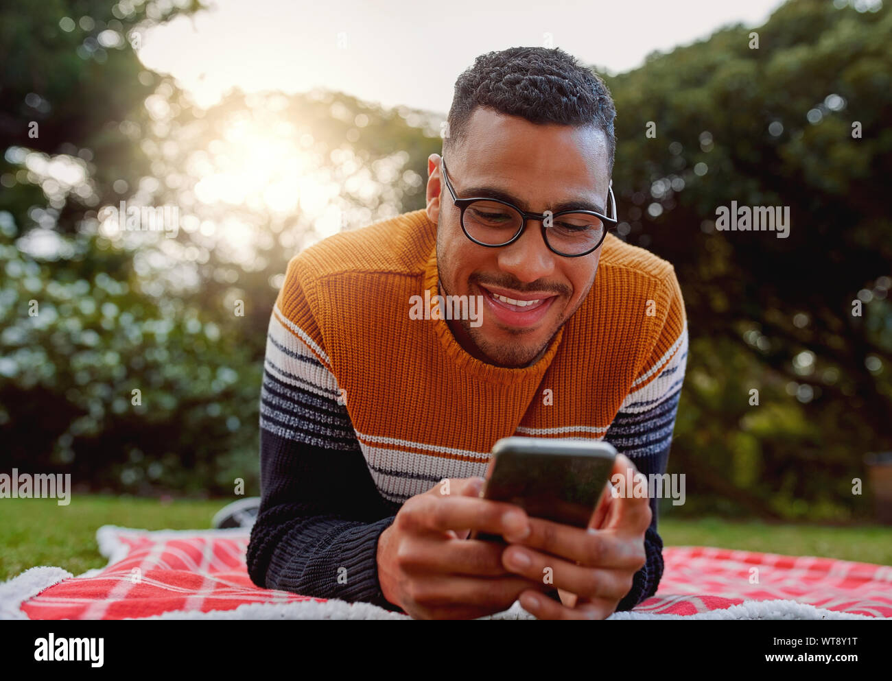 Portrait of an african smiling young man student wearing black eyeglasses relaxing in park using smart phone - college student using mobile in park Stock Photo