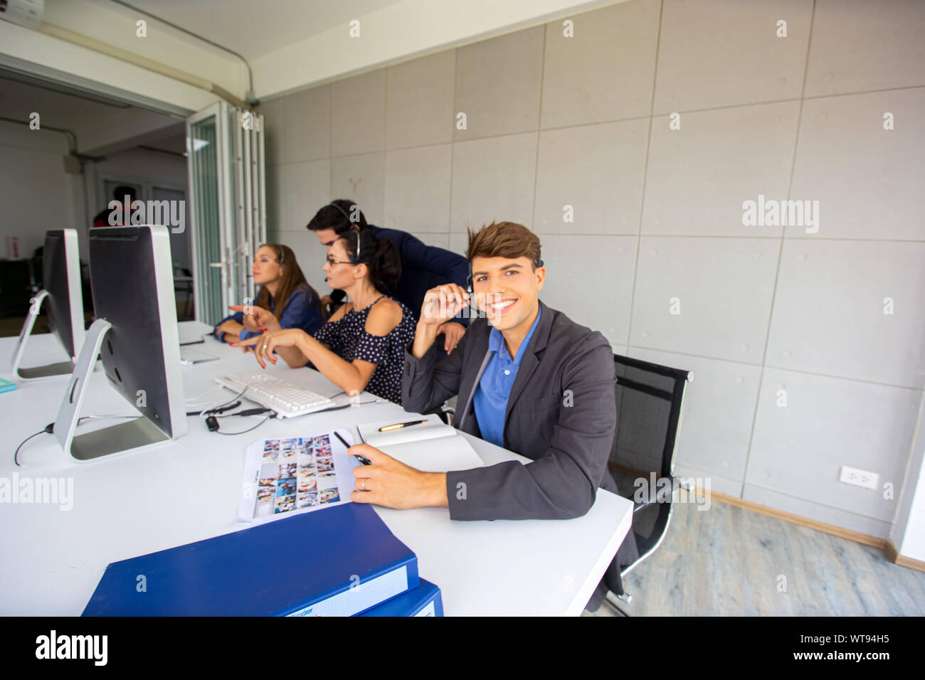 Technical support operator with headset working at laptop and computer, Business people talking on telephone with headset at office for customer help Stock Photo
