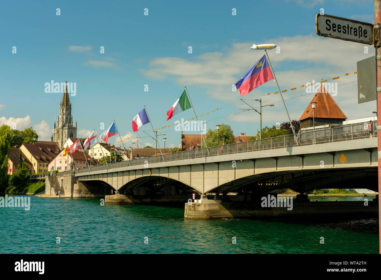 The Bridge over river Rhein, Rheinbruecke connecting the the old town and new part and Zeppelin in the sky,Konstanz, Germany Stock Photo