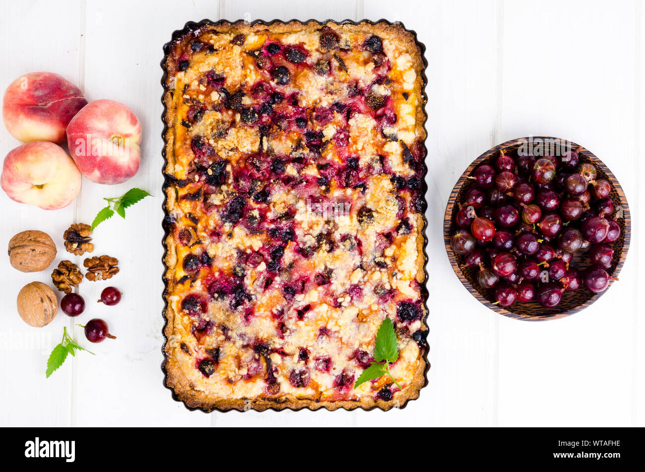 Homemade tart with berries, fruits and walnuts in shape on light background. Studio Photo Stock Photo